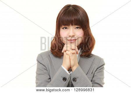 portrait of businesswoman folding her hands in prayer  on white background