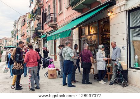 VENICE ITALY - MAY 27 2015: Crowd of people drinking and talking on the street outside wine bar in Venice Italy