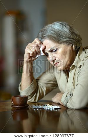 Portrait of a sick senior woman taking pills