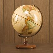 Sill life shot of a vintage world globe sitting on a desk.
