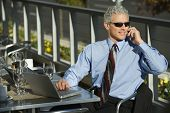 Prime adult Caucasian man in suit sitting at patio table ouside with laptop and talking on cellphone