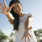 Young adult Asian female with arms and hands stretched out toward viewer.