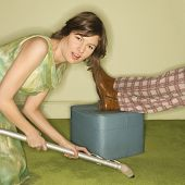 Unhappy pretty Caucasian mid-adult woman kneeling and vaccuuming carpet around male feet resting on