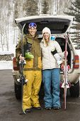 Young couple wearing winter clothes standing by automobile with ski equipment smiling.