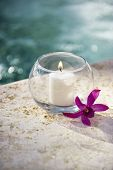 Lit candle in glass bowl with purple orchid next to pool.