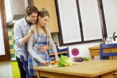 Couple Cooking Vegetables In Domestic Kitchen poster