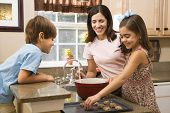 Hispanic mother and children in kitchen making cookies.