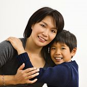 Asian mother and son hugging and smiling.