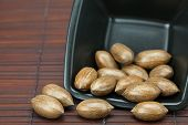 stock photo of pecan tree  - pecans in a bowl on a bamboo mat - JPG