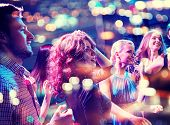 party, holidays, celebration, nightlife and people concept - smiling friends dancing in club poster