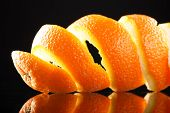 image of orange peel  - Spiral orange peel reflecting on black background - JPG