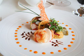 stock photo of gourmet food  - starter or entree of a french dish with seafood mixed among salad leaves - JPG
