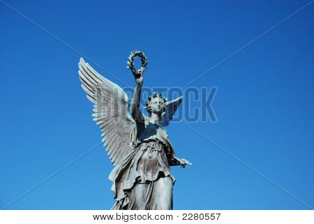 A Statue Of An Angel Reaching Up Into The Sky