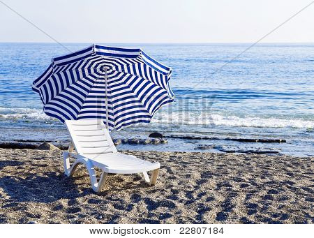 Chaise lounge with an umbrella standing alone on the bank of the blue sea