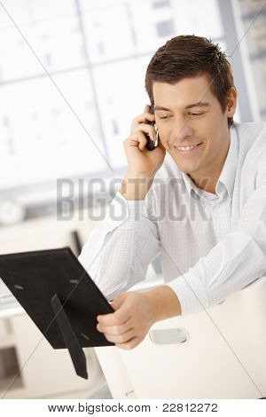 Businessman sitting in office speaking on phone, looking at photo frame, smiling.?