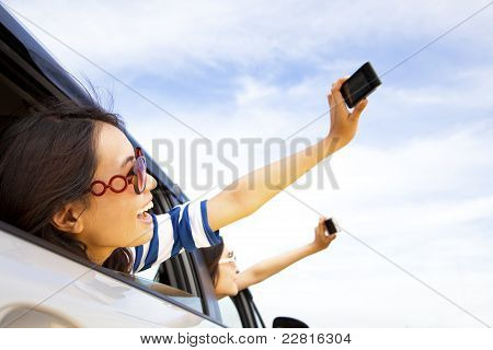 happy young woman holding camera and mobile phone taking photos