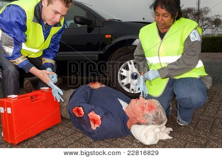 Paramedics putting on sterile gloves to care for a car crash victim  (the sleeve badges have been replaced by a non existing logo)