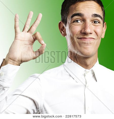 Portrait of a handsome young man smiling and gesturing okay sign against green background