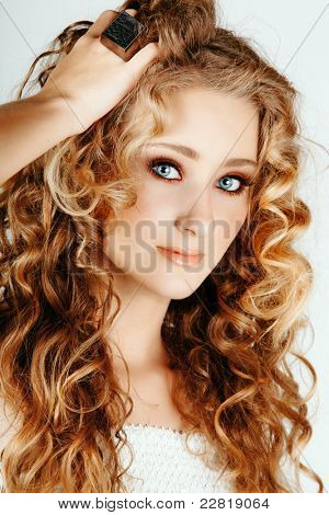 beautiful strawberry blond woman with blue eyes and long big curly hair with hand in hair