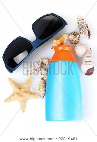 sunblock in bottle, sunglasses and shells isolated on white