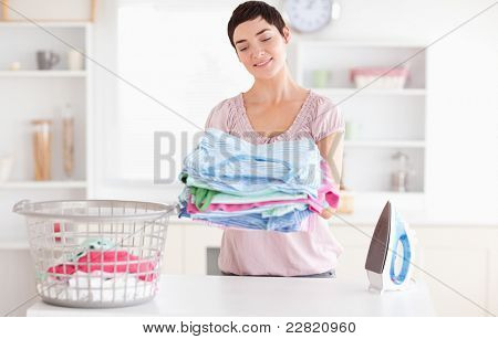 Joyful Woman with a pile of clothes in a utility room