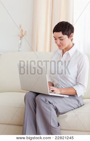 Charming Woman sitting on a sofa with a laptop in the living room