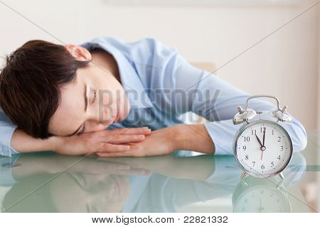 Sleeping cute woman with her head on the desk next to an alarmclock in an office