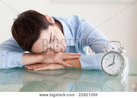 Sleeping woman with her head on the desk next to an alarmclock in an office