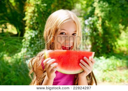 Children blond little girl eating watermelon slice in outdoor forest