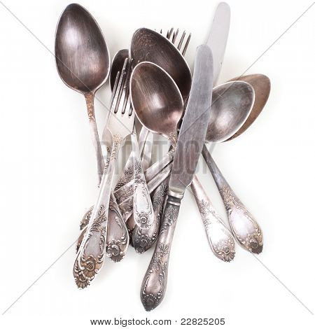 Silver spoons, forks and knifes isolated over white