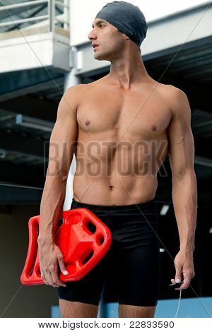 Male lifeguard at the swimming pool holding a float
