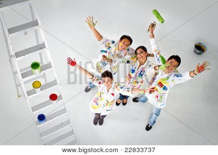 Happy group of painters holding their brushes and smiling