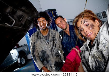 Female mechanic working on the hood of a car while colleagues watch