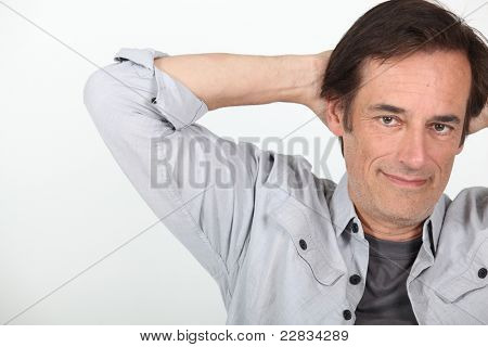 Man relaxing with arms behind head.