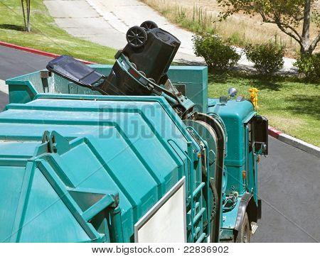 Municipal robotic arm trash truck dumps a large black can.