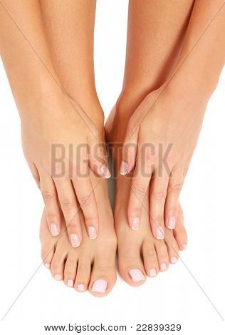 Well-groomed hands on female feet isolated on white background