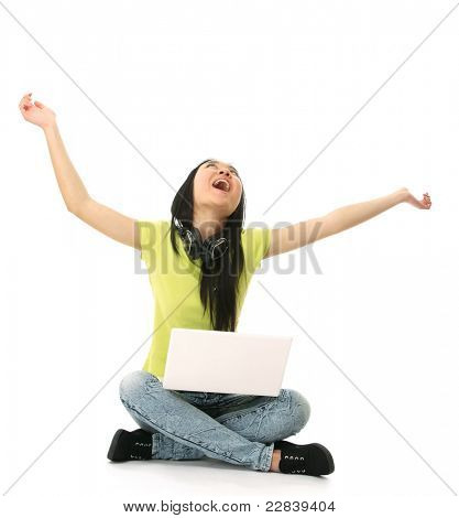 Cheerful asian woman with a laptop and headphones sitting on floor, isolated over white