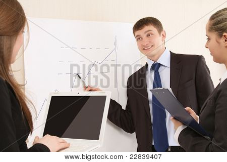 Group of business associates  discussing chart put up on the wall