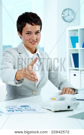 Portrait of pretty employer at workplace giving you hand for handshake