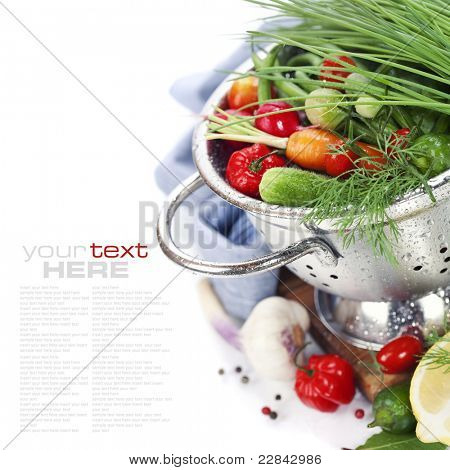 Fresh vegetables in metal colander over white (with sample text)