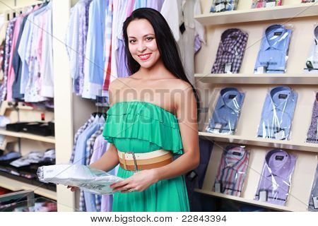 Young beautiful girl in a clothing store salesman