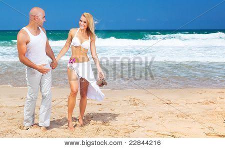 Pareja feliz caminar en la playa