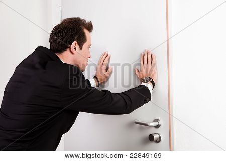 Businessman pushing the door