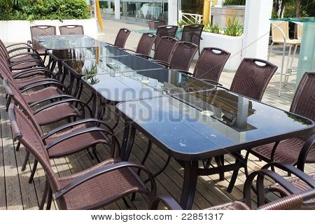 Beach cafe with  tables and chairs placed at the sea waterfront