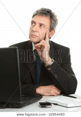 Thoughful business man working on laptop