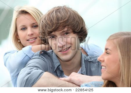 Three smiling teenagers sitting together