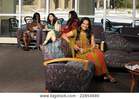Indian student with diverse group of female students dressed in traditional clothing inside school setting