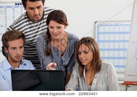 Young people gathered round a laptop