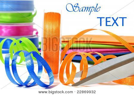 Brightly colored curling ribbon with scissors and wrapping paper on white background with copy space.  Macro with shallow dof.