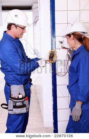 Supervisor explaining work to female electrician apprentice